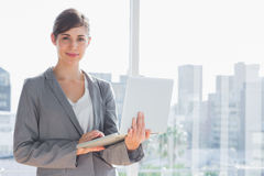 Businesswoman holding laptop Stock Images