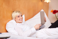 Businesswoman Holding Laptop While Lying On Bed Royalty Free Stock Photography