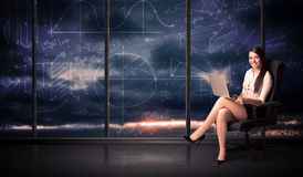 Businesswoman holding laptop in office room with graph charts on Royalty Free Stock Images