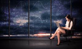 Businesswoman holding laptop in office room with graph charts on Stock Image