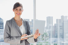 Businesswoman holding laptop and smiling at camera Royalty Free Stock Photos
