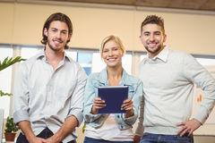 Businesswoman holding laptop standing with male colleagues Royalty Free Stock Image