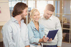 Businesswoman holding laptop standing with male colleagues Stock Image