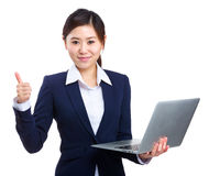 Businesswoman holding laptop with thumb up Stock Photography