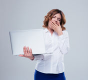 Businesswoman holding laptop and yawning Royalty Free Stock Photography
