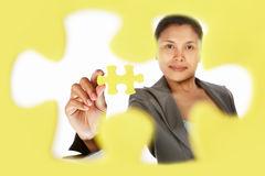 Businesswoman holding the last piece of puzzle Stock Image