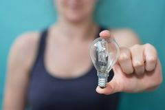 Businesswoman holding a lighbulb in her hand Stock Photo