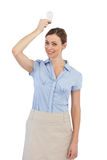 Businesswoman holding a light bulb above her head Royalty Free Stock Photos