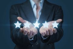 A businesswoman is holding a line of golden shining stars at the dark background stock photos