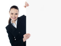 Businesswoman holding a long banner ad. Businesswoman holding a long blank banner ad isolated over white background Stock Photos
