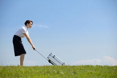 Businesswoman holding luggage in park Royalty Free Stock Photos
