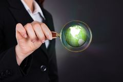 Businesswoman holding magnifying glass over globe Royalty Free Stock Photography