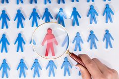 Businesswoman Holding Magnifying Over Red Human Figure. Businesswoman Holding Magnifying Over Red Figure Amongst Blue Human Figures royalty free stock image