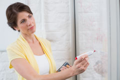 Businesswoman holding a marker and writing something. In the office stock photo