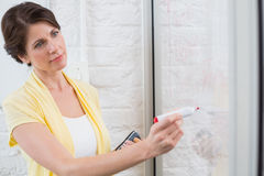 Businesswoman holding a marker and writing something. In the office royalty free stock photos