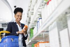 Businesswoman Holding Medicine By Shelves In Pharmacy. Portrait of young businesswoman holding medicine by shelves in pharmacy Stock Image