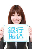 Businesswoman holding a message board with the phrase bank transfer in KANJI Stock Photo