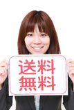 Businesswoman holding a message board with the phrase free shipping in KANJI Royalty Free Stock Photography