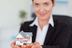 Businesswoman holding a miniature house Stock Image