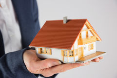 Businesswoman holding miniature model house Stock Image