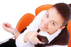 Businesswoman holding mobile-phone. Female businesswoman sitting on chair and holding mobile-phone. isolated on white background Royalty Free Stock Photo