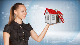 Businesswoman holding model house with tag for. Rent. Hi-tech graphs with various data as backdrop. Business concept Stock Photos