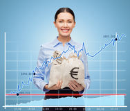 Businesswoman holding money bags with euro. Business, people, finances, investments and banking concept - young businesswoman holding money bags with euro and royalty free illustration