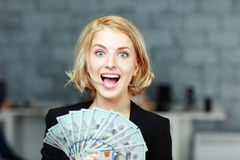 Businesswoman holding money with delight. Young businesswoman holding money with delight royalty free stock photo