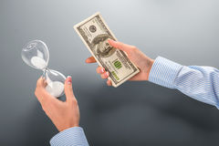 Businesswoman holding money and hourglass. Royalty Free Stock Photography