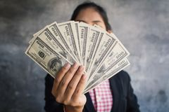 Businesswoman holding money for pay. Color of vintage tone Royalty Free Stock Image