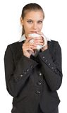 Businesswoman holding mug at her mouth Stock Photos