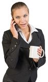 Businesswoman holding mug, talking on the phone Royalty Free Stock Photos