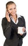 Businesswoman holding mug, talking on the phone Royalty Free Stock Photo