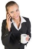 Businesswoman holding mug, talking on the phone Stock Image