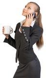 Businesswoman holding mug, talking on the phone Stock Photo