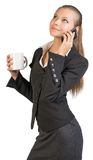 Businesswoman holding mug, talking on the phone Royalty Free Stock Photos