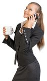 Businesswoman holding mug, talking on the phone. Looking upwards, smiling. Isolated over white background Royalty Free Stock Photos
