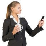 Businesswoman holding mug and using mobile phone Stock Photography