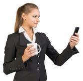 Businesswoman holding mug and using mobile phone Royalty Free Stock Photo