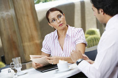 Businesswoman Holding Newspaper While Looking At Colleague Royalty Free Stock Photography