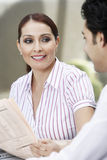 Businesswoman Holding Newspaper While Looking At Colleague Stock Photography