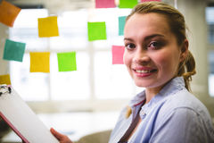 Businesswoman holding note pad against sticky notes. Portrait of smiling businesswoman holding note pad against sticky notes in creative office Royalty Free Stock Image