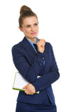 Businesswoman holding notebook and resting pen on chin, thinking Stock Images