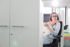 Businesswoman holding notepad while sitting on chair at creative office Stock Image