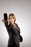 Businesswoman holding out cell phone Stock Image