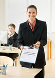 Businesswoman holding out clipboard and pen. Businesswoman holding out a clipboard and pen Royalty Free Stock Photos