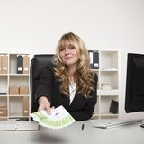 Businesswoman holding out a fistful of banknotes Royalty Free Stock Photos