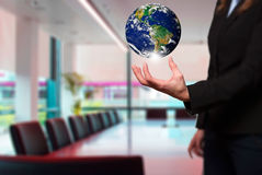 Businesswoman is holding out a Globe. Office background Stock Photos