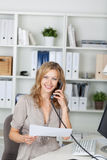 Businesswoman Holding Paper While Communicating On Landline Phon Stock Image