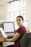 Businesswoman Holding Paper At Computer Desk Stock Image